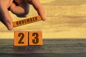 November 23rd. Day 23 Of Month, Calendar On A Wooden Cube. A Womans Hand Puts The Name Of The Month  poster