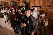 foto of antique wheelchair  - Disappointed sheriff holds empty bottle in old west tavern - JPG