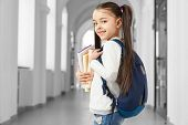 Pretty And Clever School Girl With Funny Hairstyle And Backpack On Shoulder Going Forward To Corrido poster