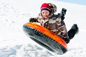 picture of inflatable slide  - A happy boy up in the air on a tube sleding in the snow.