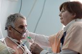 foto of oxygen mask  - Doctor is setting oxygen mask on a patient - JPG