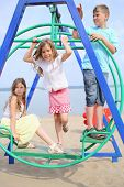 Two girls and a boy on the swing on a sunny day at the beach