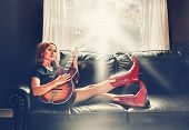 a cowgirl playing the guitar on a couch