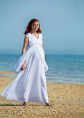 beauty pregnant woman on sea beach under blue sky
