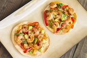 foto of jalapeno peppers  - Spicy shrimp pizza made with cumin shrimp red yellow and orange bell peppers jalapenos green onions and pepper jack cheese on a flour tortilla - JPG