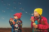 Cute little girls are blowing a soap bubble