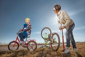 Bicycle has flat tyre and  mother helps her daughter pump it up