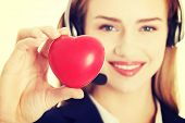 Young call center woman holding heart.