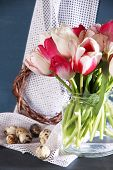Composition with Easter eggs and beautiful tulips in glass jug on color wooden background