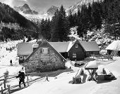 image of chalet  - Trekker leaving a chalet in the mountains - JPG