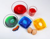 Bowls with paint for Easter eggs and eggs, isolated on white