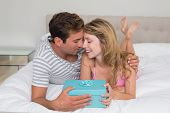 Portrait of a smiling young couple with gift box in bed at home