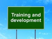 Education concept: Training and Development on road sign background