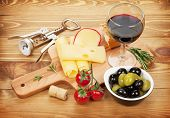 Red wine with cheese, olives, bread, vegetables and spices on wooden table