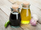 stock photo of vinegar  - Olive oil and vinegar bottles with spices over wooden table background - JPG