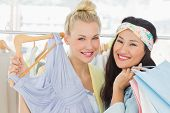 Portrait of two happy young women shopping in clothes store