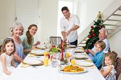 Portrait of father serving Christmas meal to family at dining table