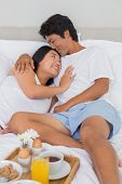 Happy couple having breakfast in bed at home in bedroom