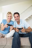 Portrait of a cheerful couple playing video games in the living room at home
