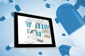 House with price tag on tablet screen against blue pills floating