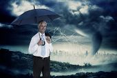 Happy businessman holding umbrella against stormy sky with tornado over cityscape