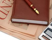 A diary and a fountain pen placed on a financial newspaper