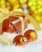 golden christmas ball on fur and gift