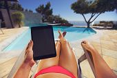 image of pov  - Young woman relaxing on a lounge chair using a tablet PC near the pool - JPG