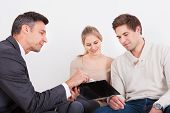Consultant Showing Clipboard To Couple