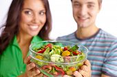 Happy couple showing vegetable salad in glass bowl