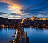 stock photo of nightfall  - Night aerial view of Prague castle and Charles Bridge over Vltava river in Prague - JPG