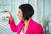 Modern business woman waiting by window in office