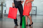 Lower section of two people in formal clothes with paper shopping bags