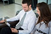 Smiling business man sitting with a female coworker looking at a tablet