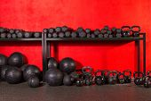 foto of dumbbell  - Kettlebell dumbbell and weighted slam balls weight training equipment at gym red walls - JPG