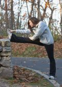 stock photo of hamstring  - Beautiful young woman stretching hamstring outdoors in park - JPG