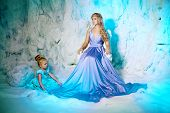 Little girl with mother in princess dress on a background of a winter fairy tale. Baby and mom snow