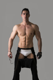 foto of strip tease  - Muscular shirtless young man with handcuffs and studded glove on grey background - JPG