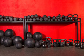 image of slam  - Kettlebell dumbbell and weighted slam balls weight training equipment at gym red walls - JPG