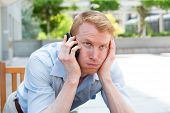 image of crap  - Closeup portrait young man annoyed frustrated pissed off by someone listening on his mobile phone bad news isolated outdoors outside background - JPG