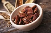 stock photo of pecan  - Pecans in the Small Wooden Bowl with Other Spices in the Background - JPG