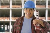 picture of adults only  - Hispanic construction worker holding level - JPG