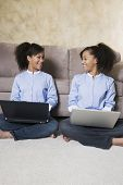 stock photo of identical twin girls  - African twin sisters with laptops - JPG