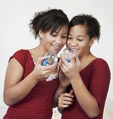 picture of identical twin girls  - African twin sisters looking at snow globes - JPG