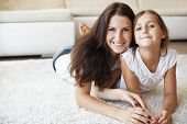 picture of preteens  - Mother with her preteen daughter having fun on a white carpet in living room at home - JPG