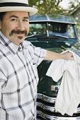 stock photo of 55-60 years old  - Hispanic man waxing truck - JPG