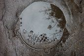 stock photo of manhole  - The puddle on the metal manhole in asphalt surface - JPG