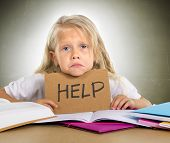 image of sad  - cute little blonde hair schoolgirl sad and frustrated holding help sign in stress with books and homework in children education concept isolated on grunge studio background - JPG