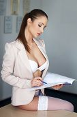 image of secretary  - Sexy brunette secretary in underwear on desk reading catalog - JPG