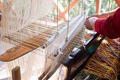 foto of handloom  - Woman weaving silk in traditional way at manual loom. Laos ** Note: Shallow depth of field - JPG